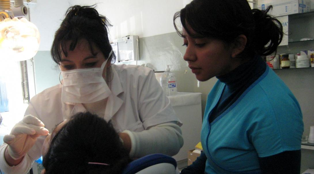 A dentist explains a dental procedure to a student doing a Dentistry internship in Argentina.